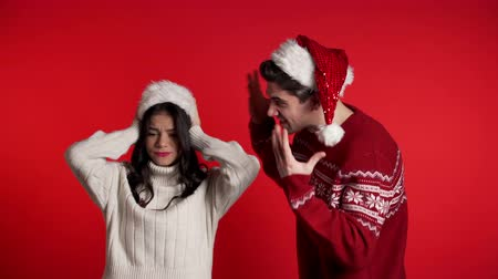 аргумент : Young man in Christmas hats emotionally screaming at his wife or girlfriend on red background in studio. Bored woman covers ears with hands. Concept of conflict, problems in relationships.