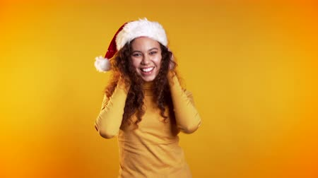 мегафон : Young cute girl smiling,dancing on yellow studio background. Woman in Santa hat. Стоковые видеозаписи