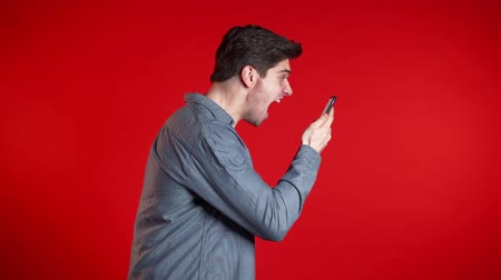 gritante : Angry modern hipster in denim shirt screaming down his mobile phone in slow motion. Stressed and depressed man on red background.