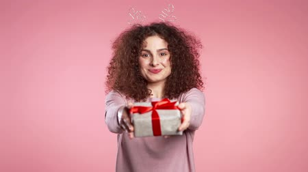 geyik : Cheerful excited woman with curly hair smiling and holding gift box on pink studio background. Cute girls portrait in deer horns wreath. Christmas mood.