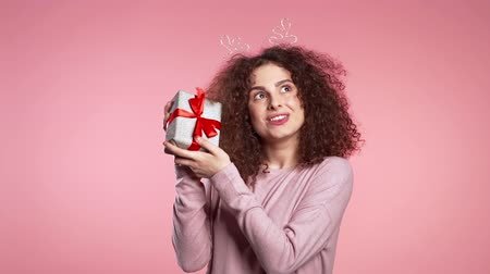 geyik : Young cute girl smiling and holding present box on pink studio background. Woman in Christmas head horns deer wreath. New year mood
