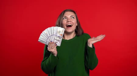 баксов : Satisfied happy excited woman showing money - U.S. currency dollars banknotes on red wall. Symbol of success, gain, victory. Slow motion