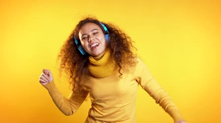 vánoční koule : Attractive woman with blue headphones dancing isolated on yellow background. Party, music, lifestyle, radio and disco concept.