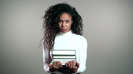 összeg : African american student woman is dissatisfied with amount of homework and books. Girl is annoyed, discouraged frustrated by studies.