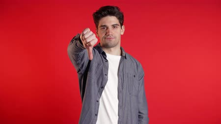 perdente : Young handsome man standing on red studio background expressing discontent and showing thumb down gesture at camera. Portrait of guy with sign of dislike.