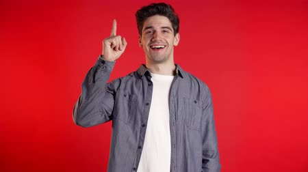 wijzer : Portrait of young thinking pondering man having idea moment pointing finger up on red studio background. Smiling happy student guy showing eureka gesture.