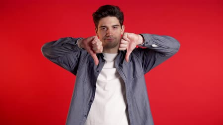 敗者 : Young handsome man standing on red studio background expressing discontent and showing thumb down gesture at camera. Portrait of guy with sign of dislike.