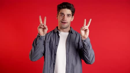 irony : Handsome man showing with hands and two fingers like quotes gesture, bend fingers isolated over red background. Very funny, irony and sarcasm concept.