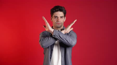rejeitar : Man disapproving with no crossing hands sign make negation gesture. Denying, Rejecting, Disagree, Portrait of handsome guy on red background Stock Footage