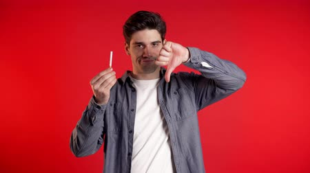 запрещенный : Young man holds cigarette, shows disapproving gesture and breaks it. Bad habit, nicotine addiction. Red studio background. Стоковые видеозаписи
