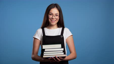bible study : Asian student girl on blue background in the studio holds stack of university books from library. Woman smiles, she is happy to graduate.