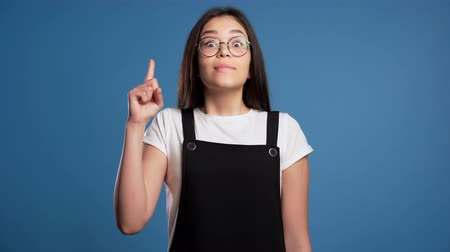 wijzer : Portrait of young asian thinking pondering girl having idea moment pointing finger up on blue studio background. Smiling happy student showing eureka gesture.
