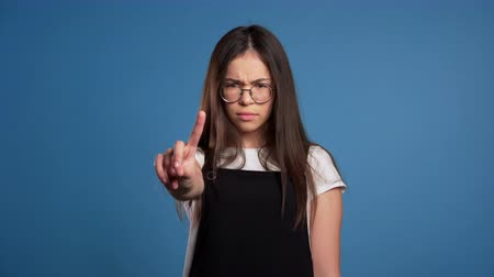 denying : Asian girl disapproving with no hand sign make negation finger gesture. Denying, Rejecting, Disagree, Portrait of pretty woman on blue background Stock Footage