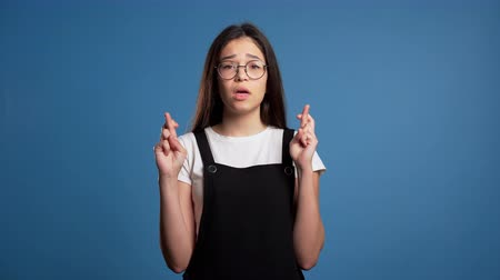 igreja : Cute asian young girl praying over blue background. Woman in glasses begging someone.