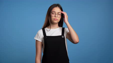 can sıkıntısı : Frustrated bored asian girl over blue wall background. Woman is tired of work or studying, she disappointed, helpless Stok Video
