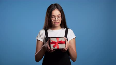 karácsonyi ajándék : Excited asian girl received gift box with bow. She is happy and flattered by attention. Girl on blue background. Studio footage. 4k