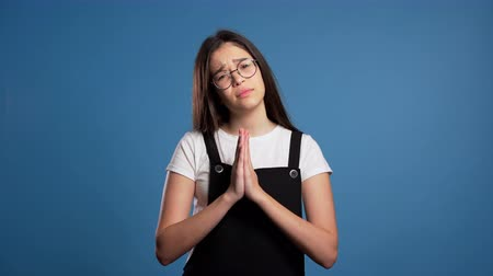 igreja : Cute asian young girl praying over blue background.