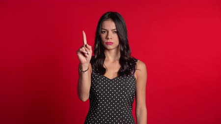 denying : Hispanic girl disapproving with no hand sign make negation finger gesture. Denying, Rejecting, Disagree, Portrait of pretty woman on red background