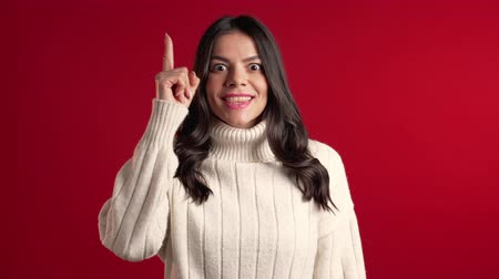 wijzer : Portrait of young hispanic thinking pondering woman in white sweater having idea moment pointing finger up on red studio background. Smiling happy girl showing eureka gesture. Stockvideo