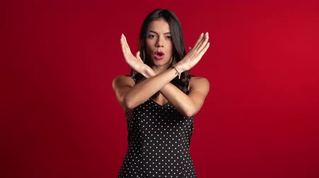 denying : Latin girl disapproving with no crossing hands sign make negation gesture. Denying, Rejecting, Disagree, Portrait of pretty woman on red background Stock Footage