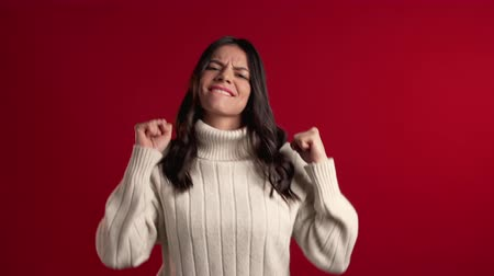 pięśc : Surprised excited happy latin woman in sweater on red background. Girl with long hair shows yes gesture of victory,she achieved result, goals.
