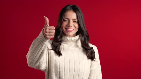 approving : Young latin woman with perfect make-up making thumbs up sign over red background. Winner. Success. Positive girl smiles to camera. Body language.