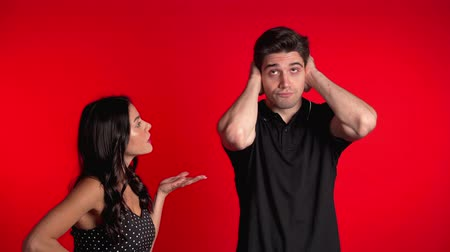 confronto : Young woman emotionally screaming at her husband or boyfriend on red background in studio. Bored man covers ears with hands. Concept of conflict, problems in relationships. Stock Footage