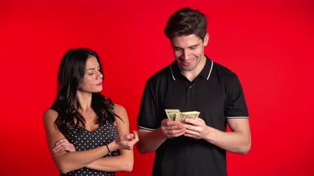 accounting : Man's hand holds out wad of money to man and under pressure from his wife, he gives her whole salary. Feminism, man henpecked Stock Footage