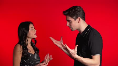 confronto : Young couple emotionally quarreling on red background in studio. Concept of conflict, problems in relationships.