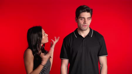 confronto : Young woman emotionally scolds her boyfriend on red background in studio. Bored man rolling his eyes. Concept of conflict, problems in relationships.