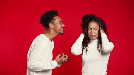 confronto : Young african man emotionally screaming at his wife or girlfriend on red background in studio. Bored woman covers ears with hands. Concept of conflict, problems in relationships. Stock Footage