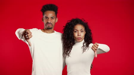 perdedor : Young african couple standing on red studio background expressing discontent and showing thumb down gesture at camera. Portrait of man and woman with sign of dislike.