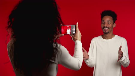 tripode : Young african girl helps her boyfriend record video blog for social network. Woman filming her husband on smartphone camera isolated on red background