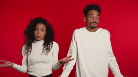 doubt : Young african unsure couple shrugs theirs arms, makes gesture of I dont know, care, cant help anything on red background.
