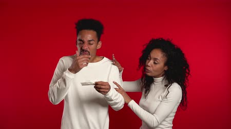zsebkendő : Young african man sneezes into tissue. Girlfriend pity, sympathize him. Isolated couple on red studio background. Guy is sick, has a cold or allergic reaction.