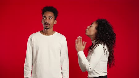 igreja : Cute african young woman begging her boyfriend or husband about something over red background.