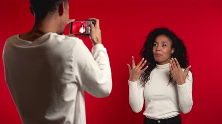 creator : Young african guy helps his girl record video blog for social network. Man filming his wife on smartphone camera isolated on red background Stock Footage