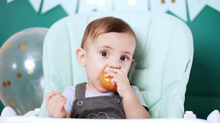 puericultura : Cute baby boy sitting in his chair and eating delicious tangerine or orange. Birthday handsome toddler child with big eyes portrait. Funny reaction. Stock Footage