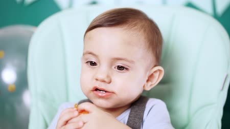 tangerina : Cute baby boy sitting in his chair and eating delicious tangerine or orange. Birthday handsome toddler child with big eyes portrait. Funny reaction. Vídeos