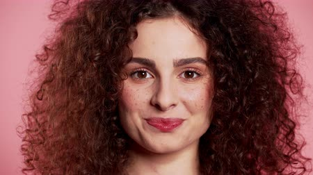 boss : Young curly woman with trendy glitter freckles make-up. Portrait of flirting beautiful girl on pink studio background.
