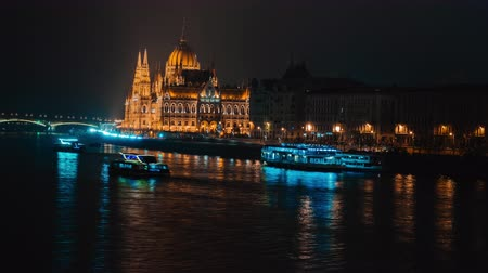 венгерский : Time Lapse panorama night view on Danube and Hungarian Parliament in Budapest, Hungary. Beautiful evening or night scene of illuminating ancient architecture and river cruise boats.