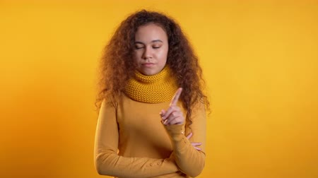 denying : Pretty girl disapproving with no crossing hands sign make negation gesture. Denying, Rejecting, Disagree, Portrait of woman on yellow background. Stock Footage
