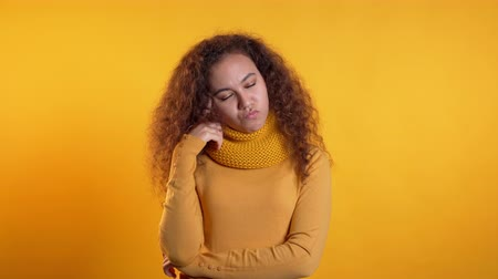 contemplative : Thinking woman looking up and around on yellow background. Worried contemplative face expressions. Pretty curly girl model