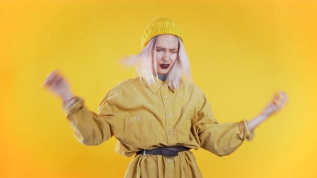 geeuwen : Young upset woman with pink hair, studio portrait. Girl putting hands on head, isolated on yellow background. Concept of problems and boredom