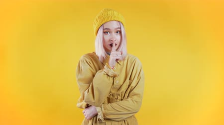 forefinger : Positive girl holding finger on her lips over yellow background. Gesture of shhh, secret, silence. Close up. Body language. Young punk woman Stock Footage