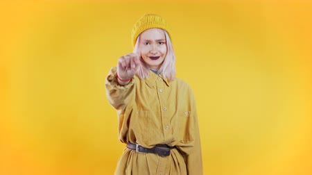 denying : Pretty unusual girl disapproving with no crossing hands sign make negation gesture. Denying, Rejecting, Disagree, Portrait of woman on yellow background. Stock Footage
