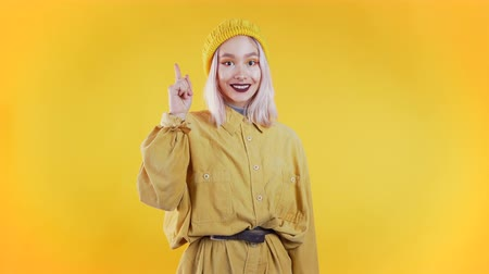 direto : Portrait of young thinking pondering woman having idea moment pointing finger up on yellow studio background. Smiling happy girl showing eureka gesture.