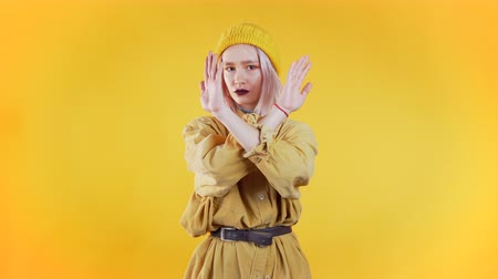denying : Cute girl disapproving with no crossing hands sign make negation gesture. Denying, Rejecting, Disagree, Portrait of pretty woman on yellow background Stock Footage