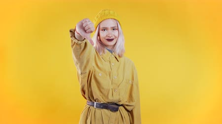 looking down : Young pretty woman standing on yellow studio background expressing discontent and showing thumb down gesture at camera. Portrait of girl with sign of dislike Stock Footage