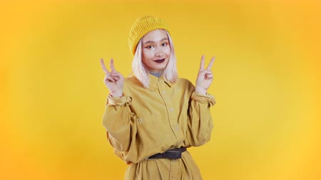 irony : Pretty punk girl showing with hands and two fingers like quotes gesture, bend fingers isolated over yellow background. Very funny, irony and sarcasm concept.